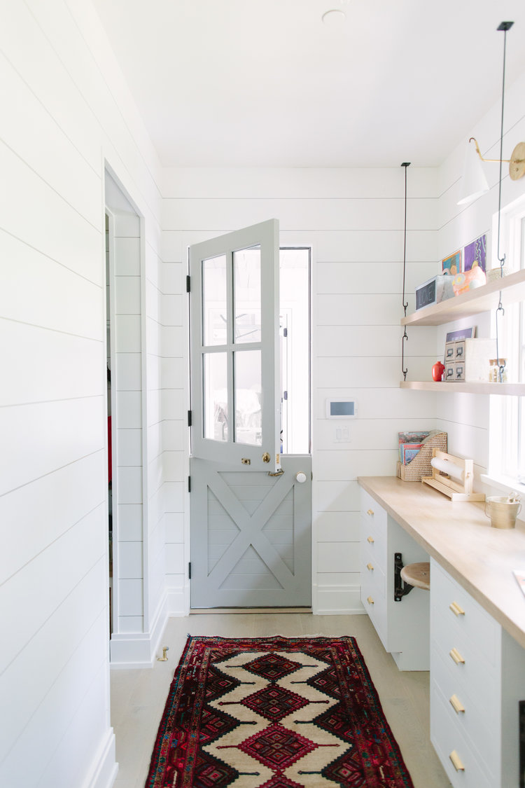 Serene and enchanting, a light grey painted Dutch door opens into a welcoming home with interior design by Kate Marker in Barrington, IL. #interiordesign #dutchdoor #serenedecor