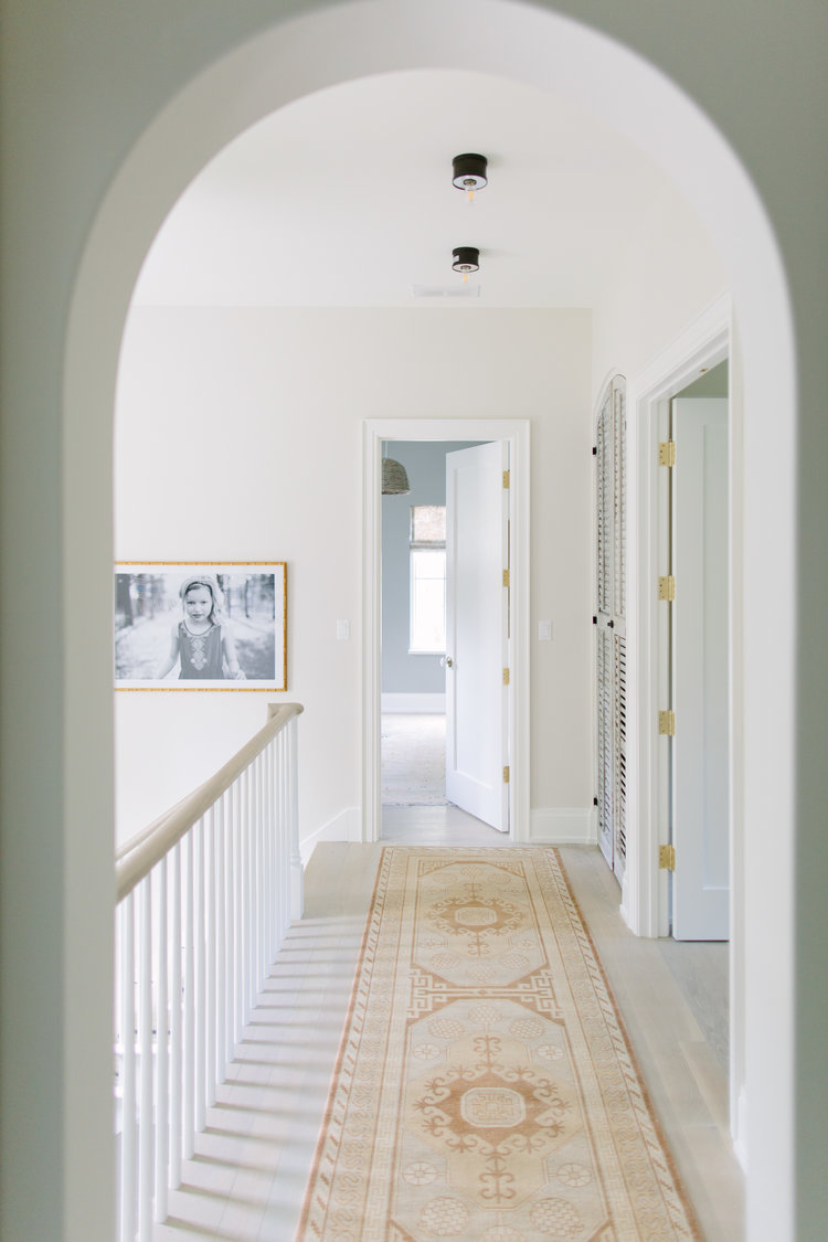 Archways and reclaimed materials come together in a beautiful hall within a home by Kate Marker in Barrington, IL. #interiordesign #archway #serenedecor