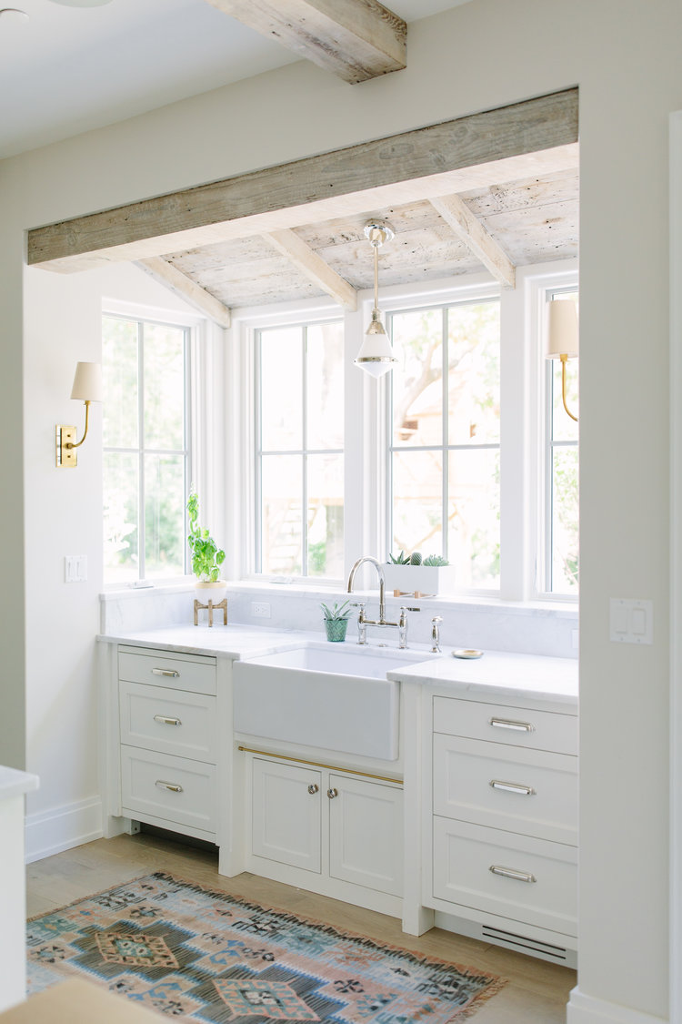 Charming modern farmhouse sink bay in a kitchen with rustic wood ceiling and design by Kate Marker in Barrington, IL. #modernfarmhousekitchen #farmsink #serenedecor