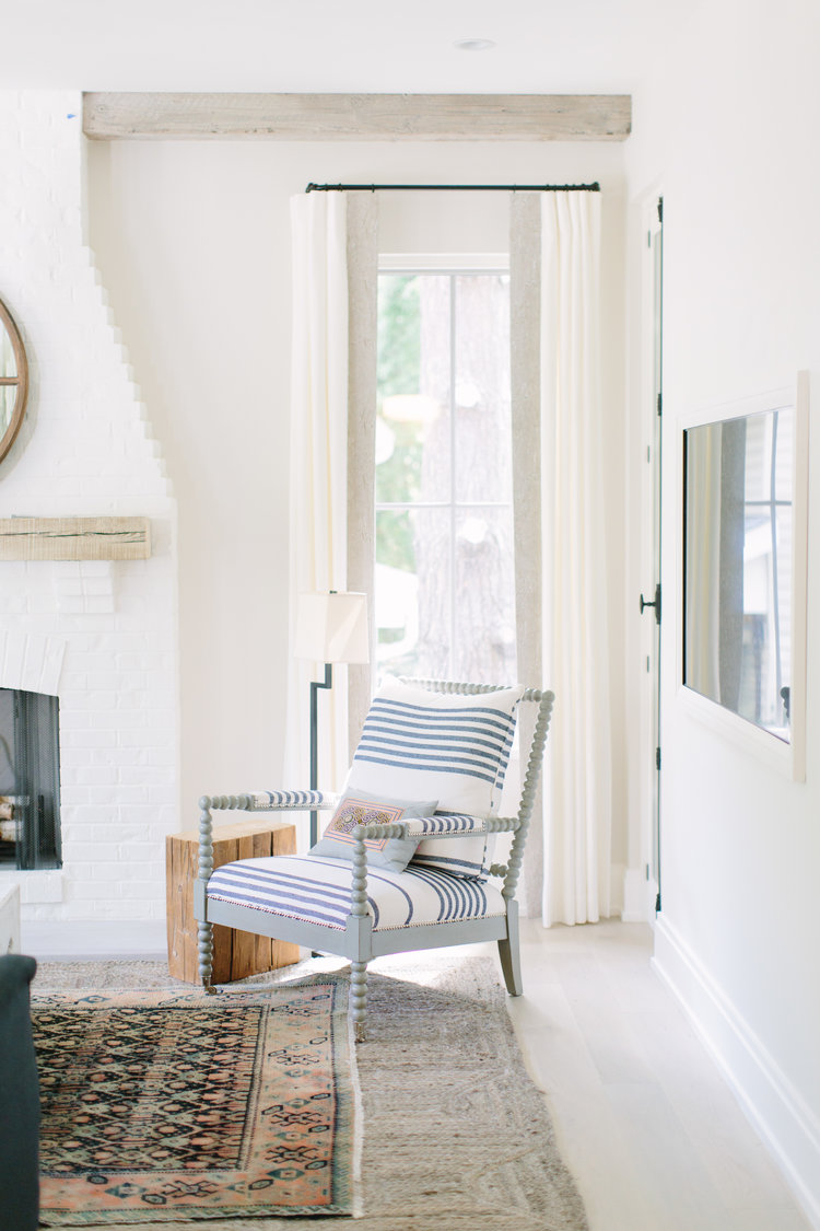 White and bright modern farmhouse living room with spindle chair and design by Kate Marker in Barrington, IL. #modernfarmhouse #livingroom #serenedecor