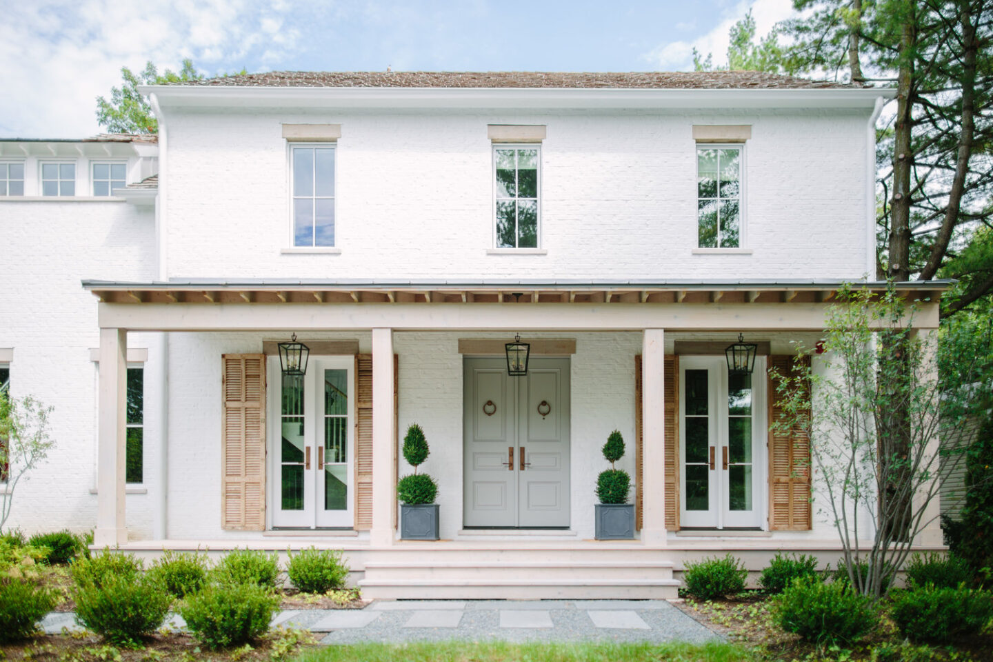 Charming and romantic modern farmhouse exterior facade with lime washed brick, rustic natural wood shutters, and light grey front door. Interiors by Kate Marker in Barrington, IL. #houseexterior #housedesign #modernfarmhouse #whitebrick #curbappeal #greyfrontdoor