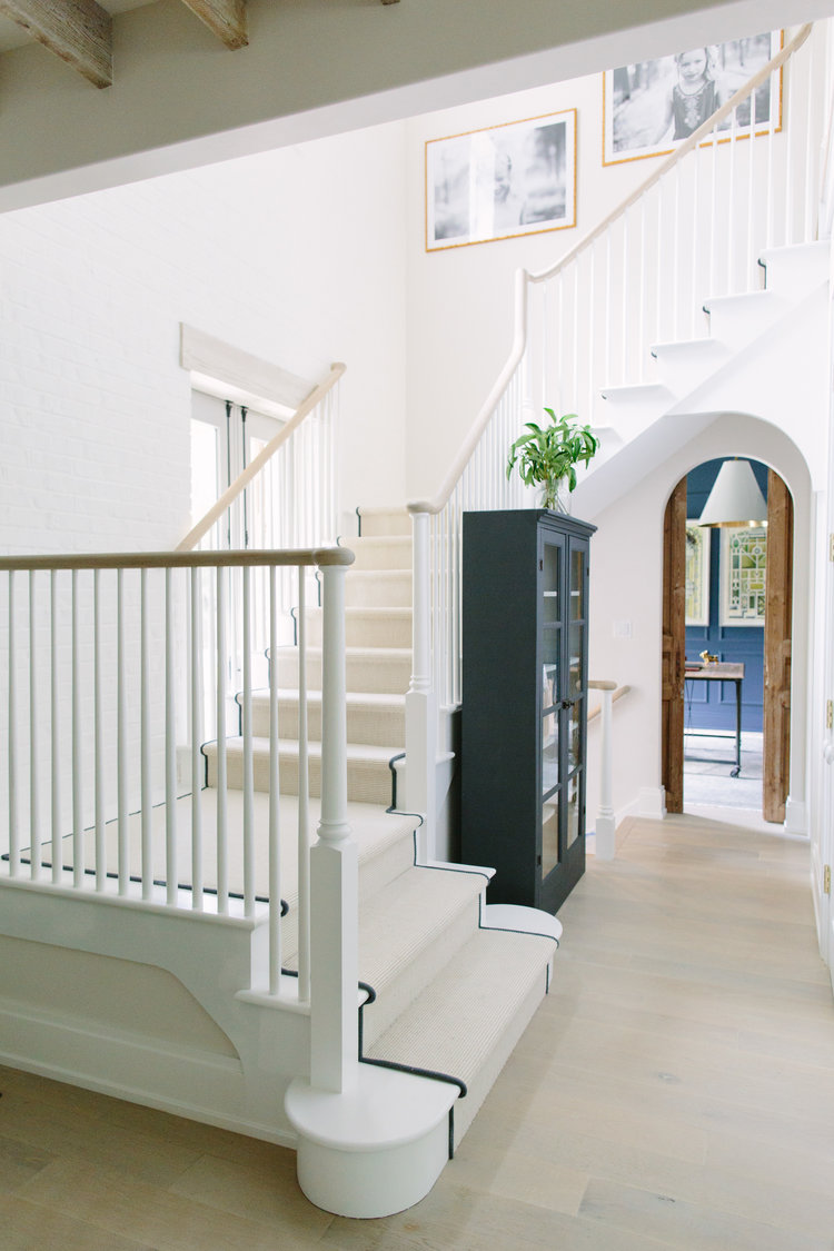 Magnificent staircase and archways in a beautiful modern farmhouse with interior design by Kate Marker in Barrington, IL. Come enjoy encouraging love quotes and timeless decor inspiration! #modernfarmhouse #staircase #interiordesign