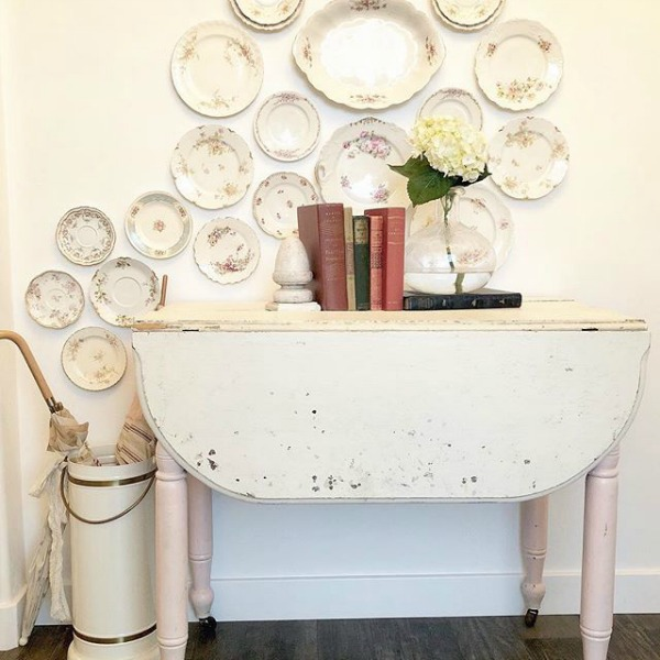 Rustic white country dropleaf table and a collection of vintage plates hung on the wall for a whimsical display by Le Cultivateur. Come see White & Rustic Country Interiors: 19 Ideas to Add Whimsy. #countrydecor #countrystyledecorating #vintageplates #rusticcountrydecor #whitemodernfarmhouse