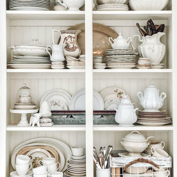 Rustic white beadboard backed shelves in a country cabinet filled with white vintage treasures - Le Cultivateur. #whitecountrydecor #countrycabinet #beadboard #toneontone #vintagestyle