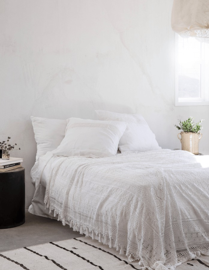 Warm minimal modern rustic luxe bedroom with white lace bedspread (Shabby Chic's Cluny) designed by Leanne Ford for HGTV's Rock the Block. #leanneford #bedroomdesign #rusticmodern #interiordesign #whitebedroom