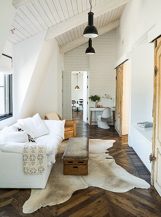 Warm minimal, modern rustic boho interior design with white sofa, cowhide, and vintage - design by Leanne Ford. #leanneford #interiordesign #roughluxe #minimaldecor #vintageboho