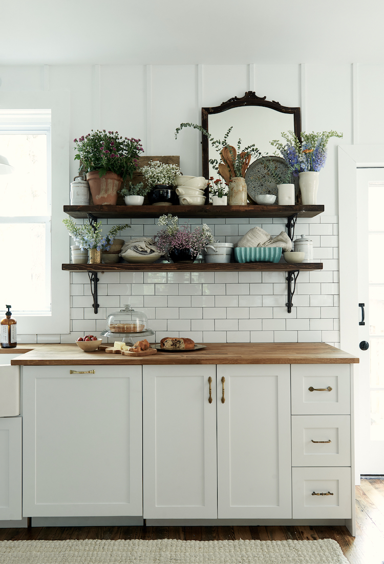 Farm sink, subway tile backsplash, and open shelving in a modern farmhouse kitchen by Leanne Ford. #restoredbythefords #leanneford #modernfarmhousekitchen #farmsink #modernrustic #interiordesign