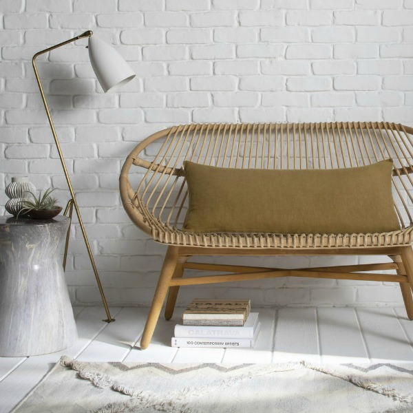 Parachute Home linen lumbar pillow in ochre upon an airy rattan settee with modern floor lamp. #ochrepillow #modernboho #interiordesign