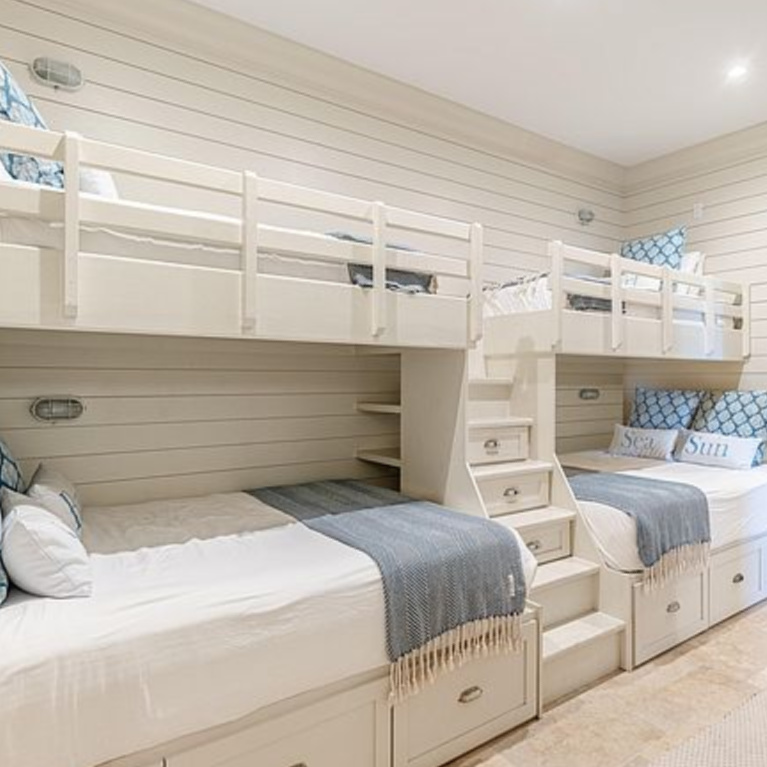 Bunk room with coastal style and blue accents in a luxurious Inlet Beach, FL home. #bunkrooms #coastalstyle