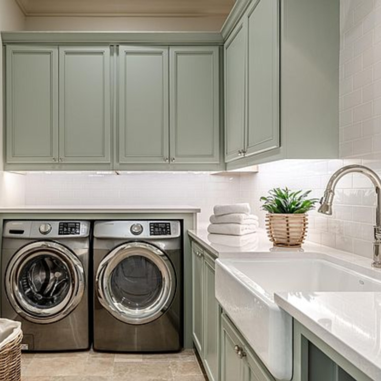 Laundry room with farm sink and tranquil color palette in a coastal home in Inlet Beach, FL. #laundryroom #coastalstyle