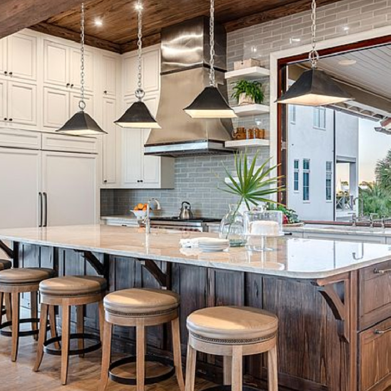 Charming coastal kitchen with wood ceiling and island in a luxurious Inlet Beach, FL home. #coastalkitchen #woodceiling