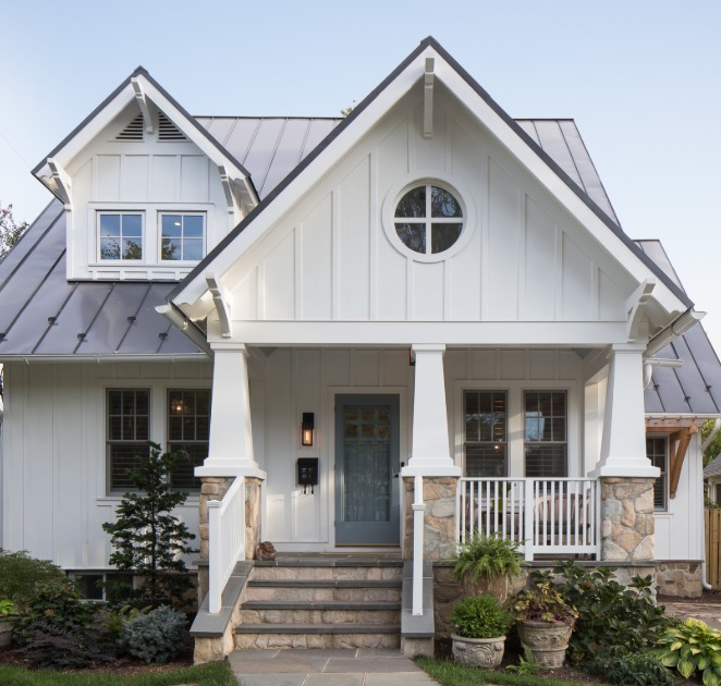 Charming white Craftsman house exterior with board and batten, round window, and stone detail = Red House Architects. #craftsmanstyle #housedesign #houseexteriors #boardandbatten