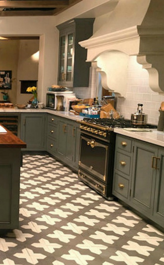 Robert and Sol's kitchen from Grace and Frankie has gorgeous Spanish cement tile, grey cabinets, and La Cornue stove with subway tile backsplash. #graceandfrankie #robertandsol #setdesign #kitchendesign #spanishtile #kitchenisland #lacornue