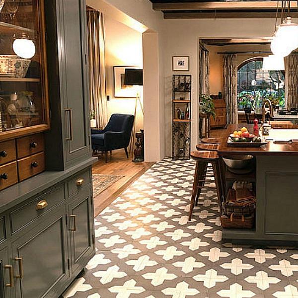 Robert and Sol's kitchen from Grace and Frankie has gorgeous Spanish cement tile, grey cabinets, and La Cornue stove with subway tile backsplash. #graceandfrankie #robertandsol #setdesign #kitchendesign #spanishtile #kitchenisland