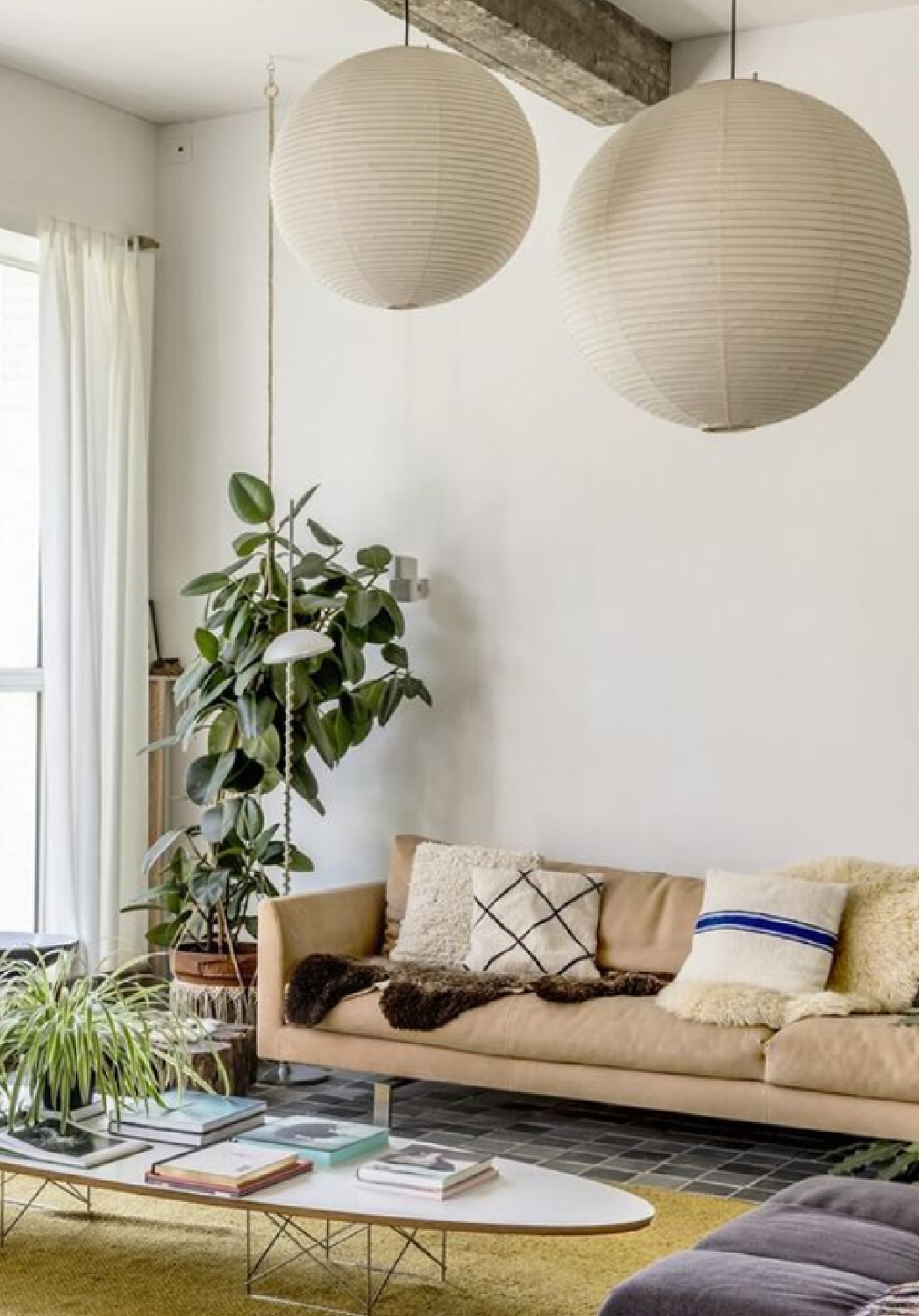 Scandi style living room with dramatic woven lanterns, houseplants, neutrals, and midcentury style - Elle Decor Sweden.