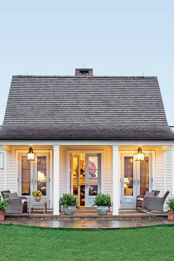 Adorable white house exterior with three sets of French doors - Lucy Williams.