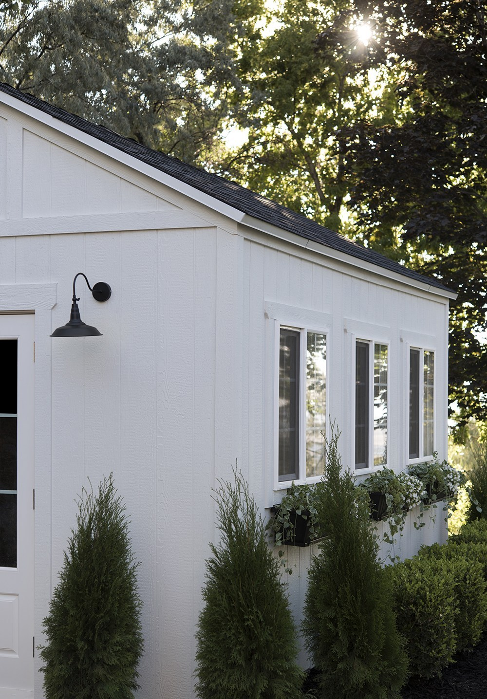 Nuance (Sherwin Williams) is name of white paint on this shed exterior with windows and window boxes - RoomforTuesday. #nurance #whitepaintcolors #exteriorcolors