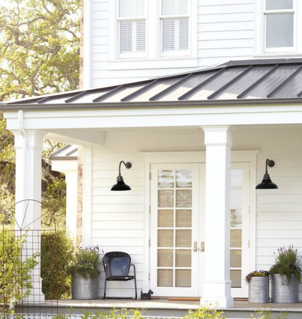 Beautiful white modern farmhouse porch and exterior with metal roof and dome shade barn style sconces from Rejuvenation. #modernfarmhouse #houseexterior #metalroof #barnlights