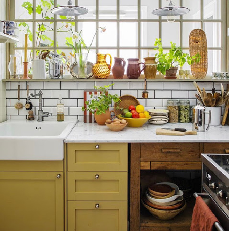 Warm yellow painted kitchen cabinets and subway baksplash in a cheerfully organic space - via designindulgence. #yellowabinets #kitchendesigns