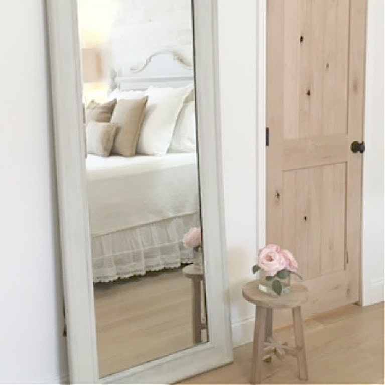 Serene airy bedroom with cottage style furniture and knotty alder doors as well as white oak hardwoods - Hello Lovely Studio.