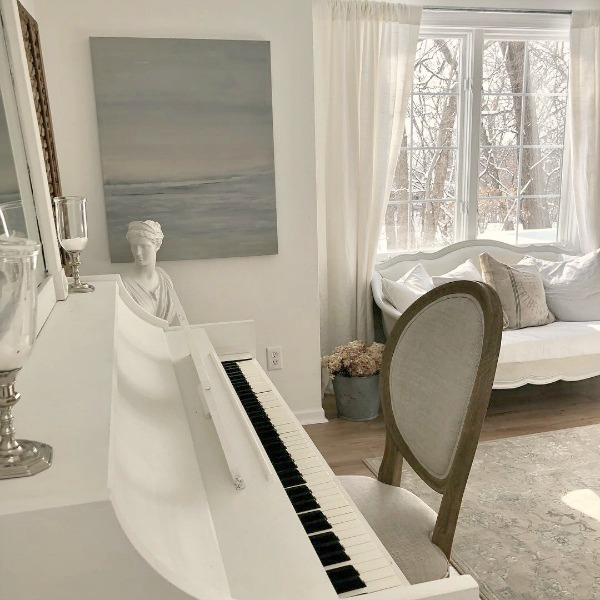 Hello Lovely's serene studio with white piano, French settee, and original painting. #hellolovelystudio #nordicfrenchstyle #serenedecor #whitepiano
