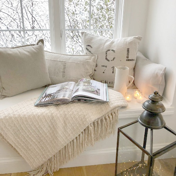 Tone on tone palette at cozy window seat with pillows and candlelight - Hello Lovely Studio. #windowseat #allwhitedecor #scandinavianstyle #interiordesign