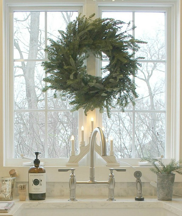 Frasier fir wreath at kitchen sink window in Hello Lovely Studio's French Nordic kitchen with farm sink. Find a Soft, Ethereal European Country Kitchen Mood to Inspire Now!