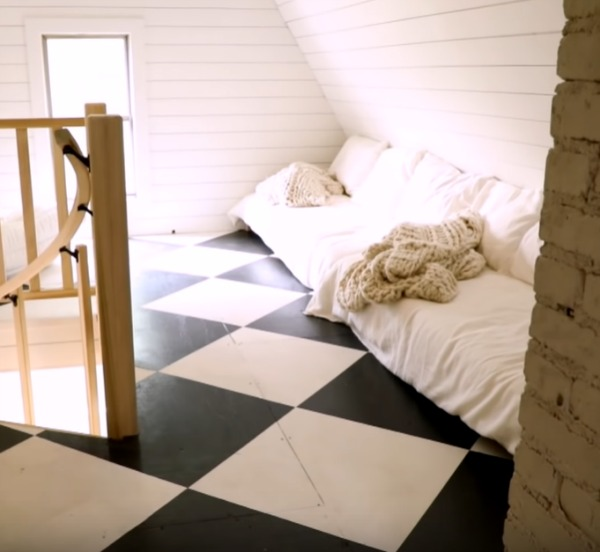 Black and white checkered painted wood floor in an attic with paneled walls and white bedding with cable knit throws. Design by Leanne Ford. #leanneford #whitedecor #blackandwhite #interiordesign
