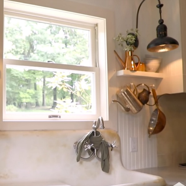 Beadboard on walls, white Shaker cabinets, and a vintage farm sink play starring roles in a cottage kitchen with rustic luxe style from Leanne Ford. #rusticdecor #kitchendesign #leanneford