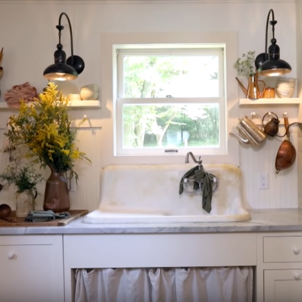 Rustic kitchen with vintage sink with skirt, beadboard, Shaker cabinetry, and pegs for vintage kitchenware. Come steal Leanne Ford's Paint Colors in the Sweetest Country Cottage!. #vintagekitchen #interiordesign #leanneford #ppgsugarsoap #ppgdelicatewhite #paintcolors