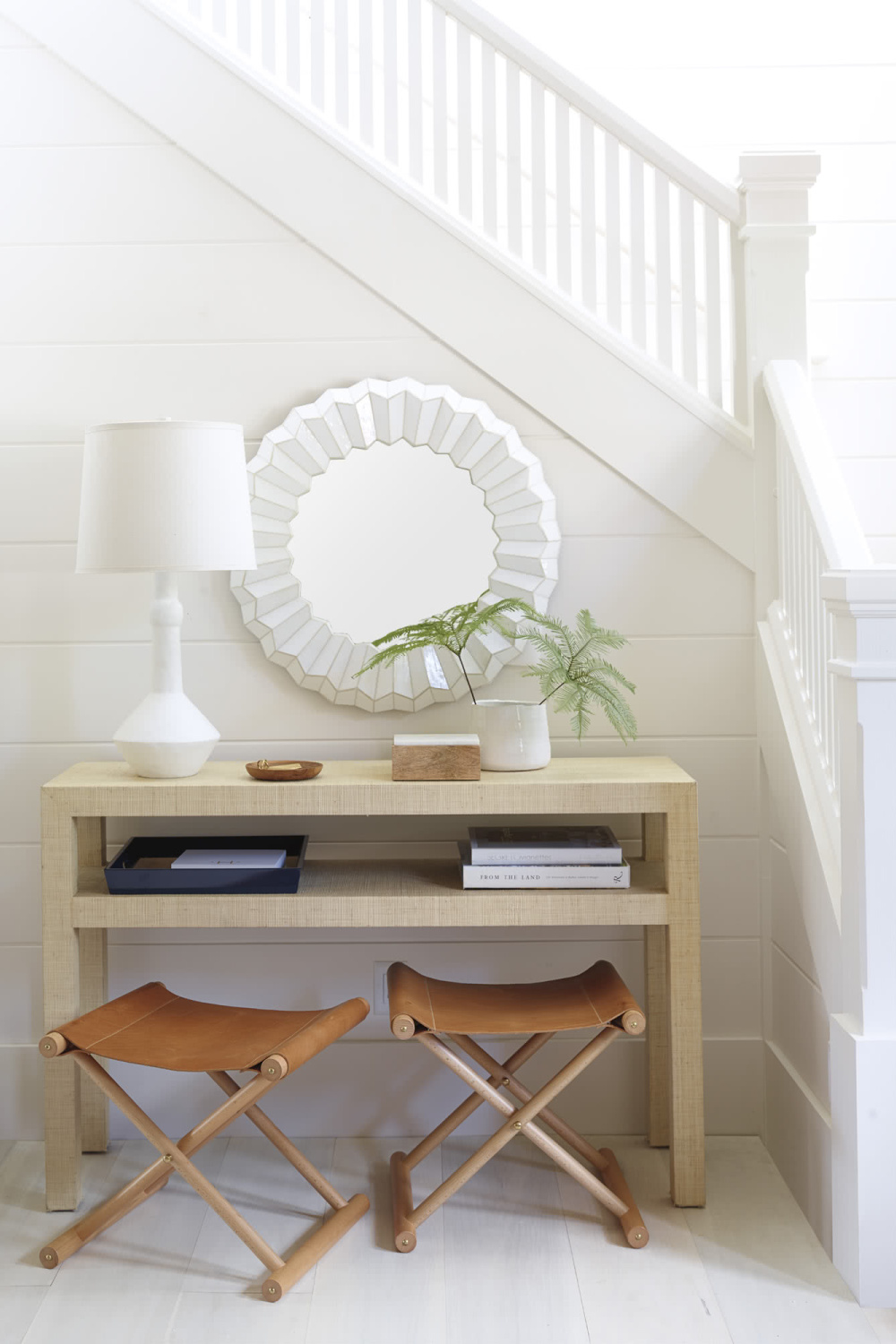 Classic, airy white entry area near staircase in a coastal cottage with Cooper leather stools from Serena & Lily. #leatherstool #foldingstools #coastalfurniture #entry