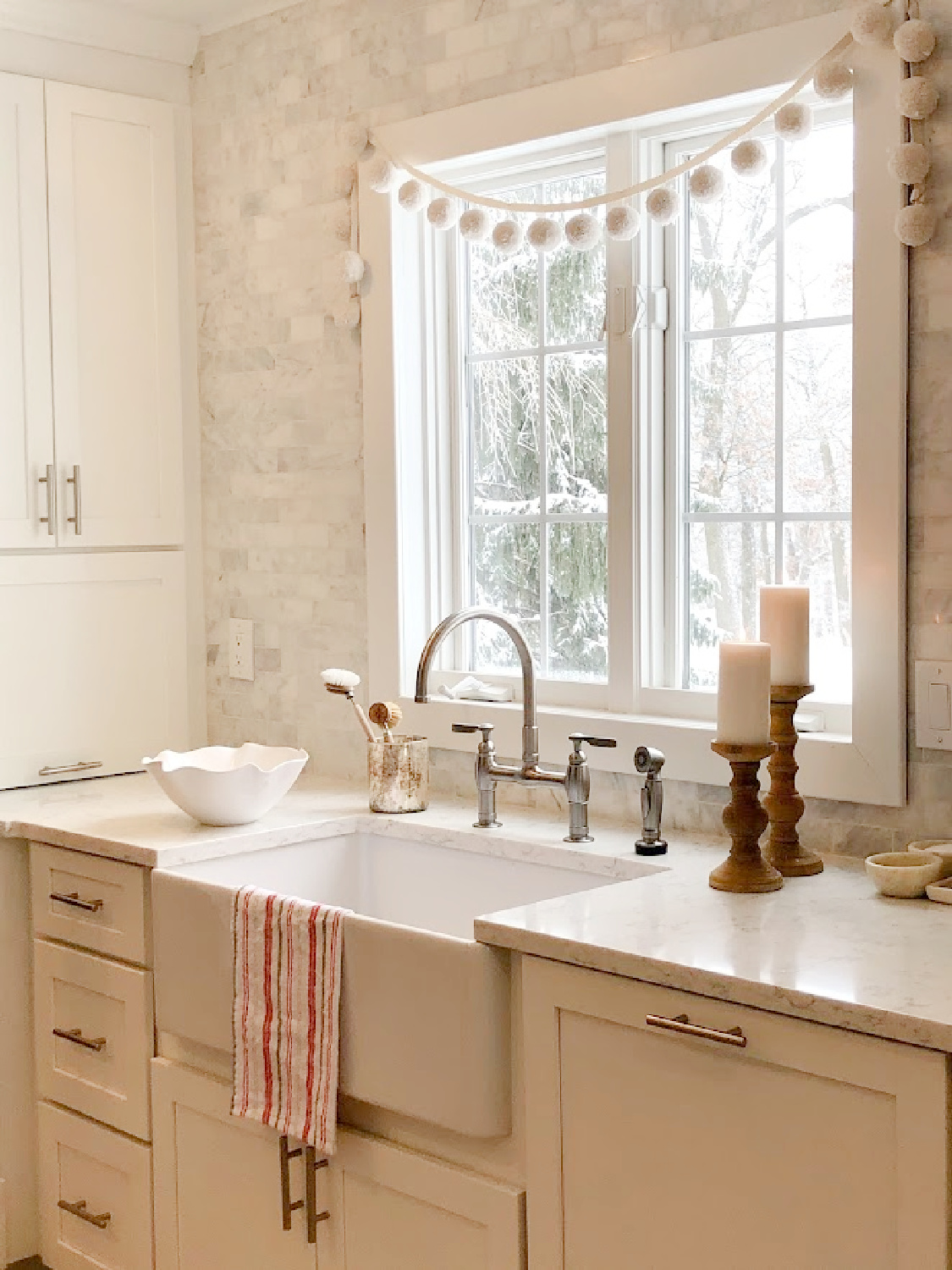 Serene European country farmhouse kitchen with farm sink, Viatera Minuet counters, and marble subway tile backsplash - Hello Lovely Studio.