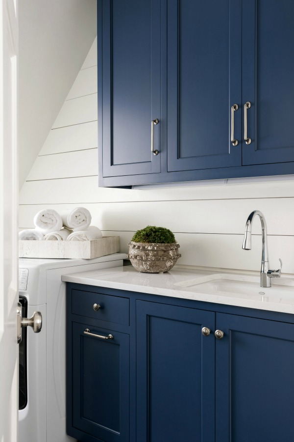 Shiplap walls and blue cabinets in a classic laundry room designed by Sherry Hart (Brookhaven). #laundryroom #shiplapwalls #bluecabinets #interiordesign