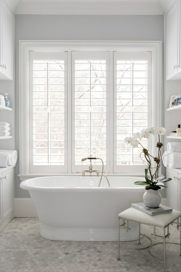 Luxurious white bathroom with freestanding tub, plantation shutters, and marble mosaic tile floor - design by Sherry Hart. #luxuriousbathroom #whitebathroom #bathroomdesign #freestandingtub #plantationshutters