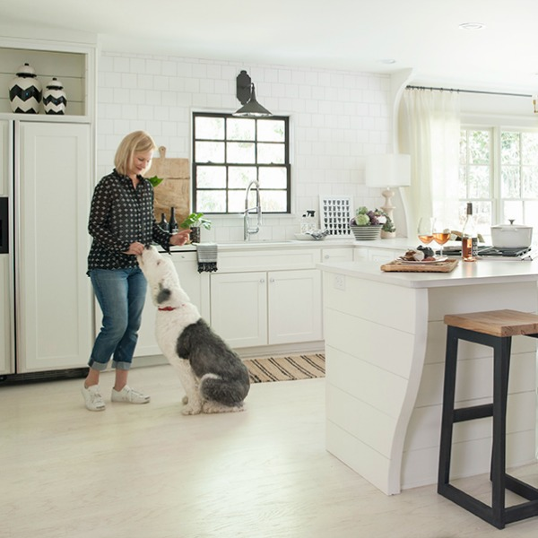 Sherry Hart and her Old English Sheepdog in her beautiful white Atlanta kitchen with shiplap and architectural interest. #whitekitchen #interiordesign #kitchendesign