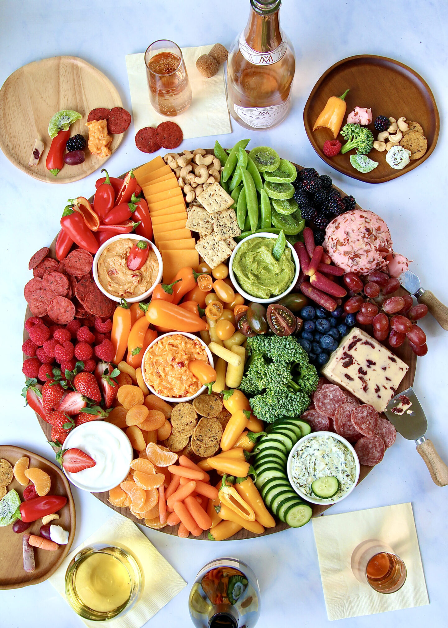 Rainbow colors on this pleasing and appetizing spring snack board by Maegan Brown of The Baker Mama! #snackboards #grazeboards #appetizers #rainbow