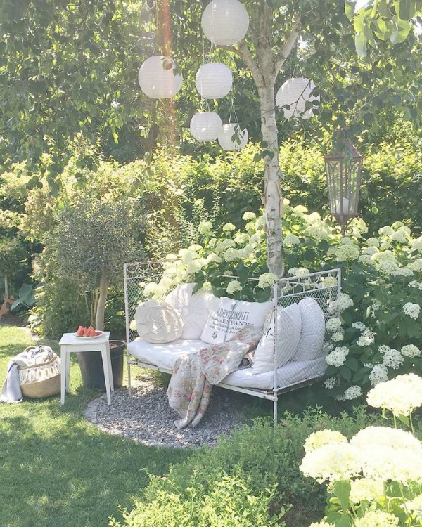 Enchanting garden with romantic daybed and paper lanterns in trees - Villa Jenal. #cotagegarden #daybed #frenchnordicstyle #romanticdecor