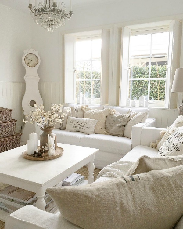 Serene and spare all white Scandi style living room with Mora clock - Villa Jenal. #frenchnordicstyle #nordicfrench #livingroom #swedishdecor #moraclock #interiordesign
