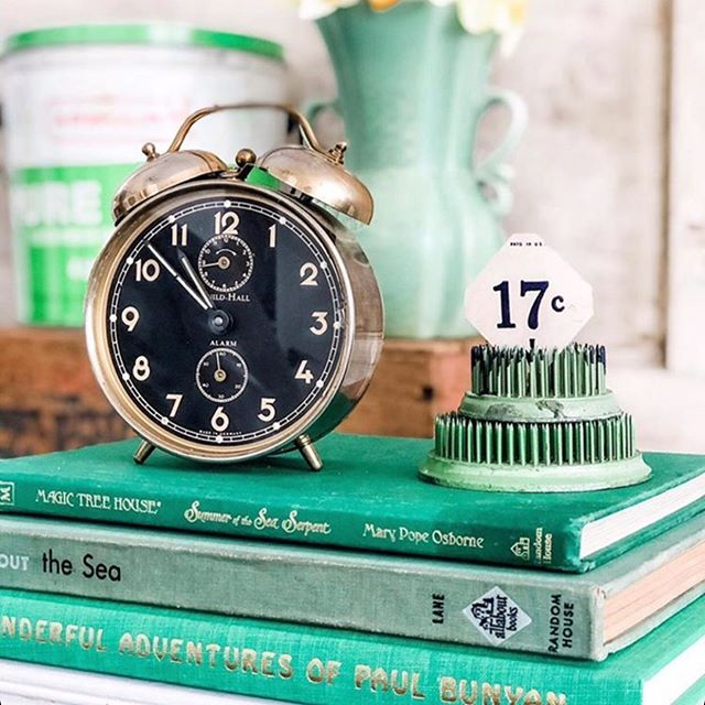 Spring green vintage books, alarm clock, and vintage treasures in a vignette by Le Cultivateur. #vintagestyle #green #vintagebooks #springgreen