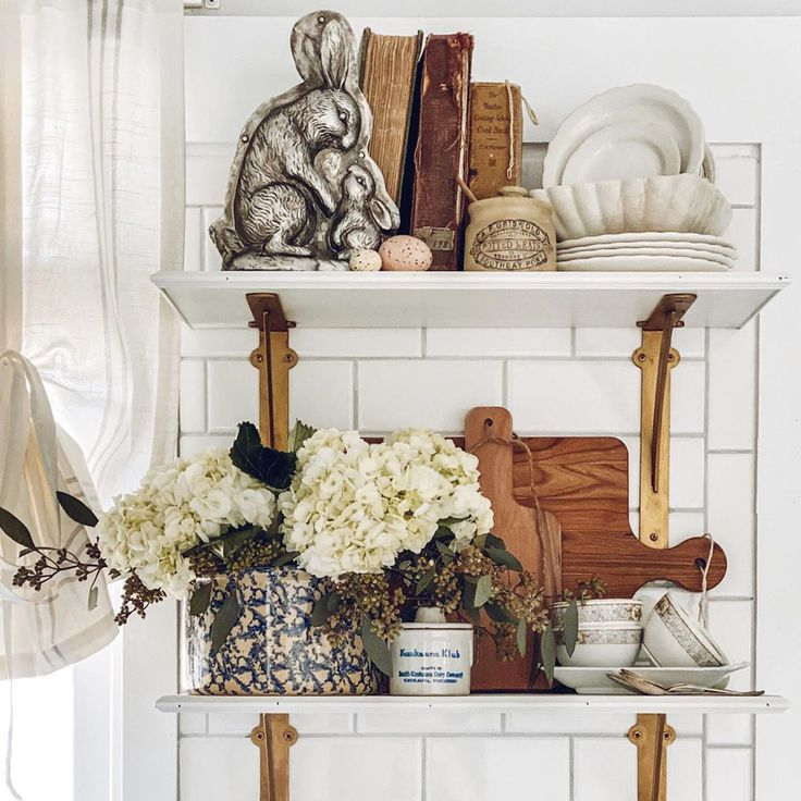 French farmhouse vintage decor on lovely white shelves in a kitchen - design by Le Cultivateur. #frenchfarmhouse #interiordesign #decorating #openshelving #vintagestyle