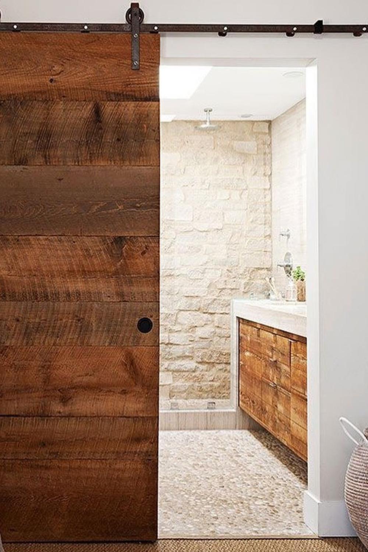 Wabi sabi natural and organic bathroom design with sliding barn door and stone clad wall - via Nuances de Vert. #organicdesign #wabisabi #bathroomdesign