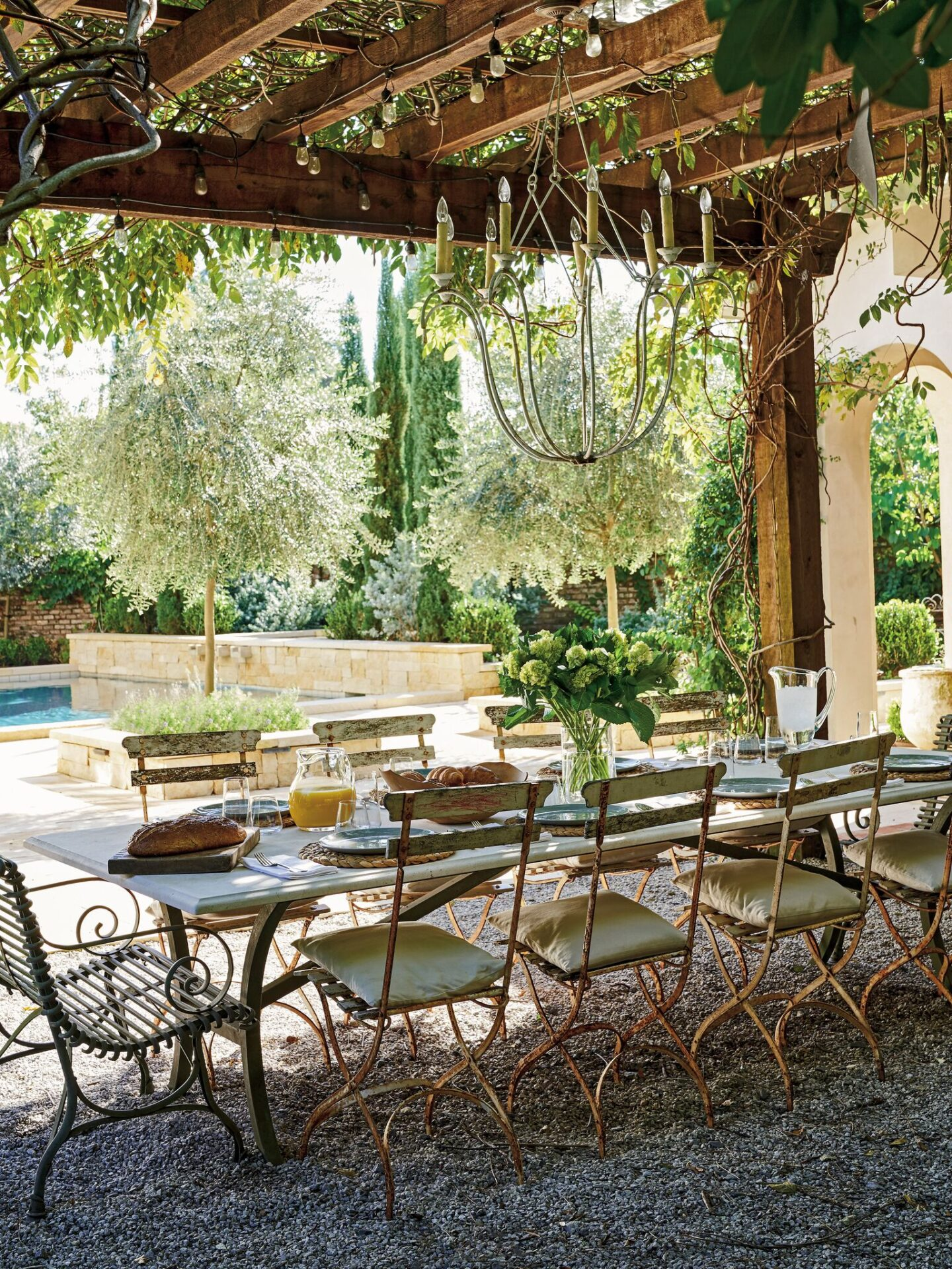 This outdoor dining area designed by Tara Shaw is an oasis with wisteria arbor, vintage tables and chairs, iron chandelier and pea gravel. #frenchgarden #frenchcourtyard #outdoordining #oldworldstyle #antiques #outdoooasis #romanticdecor