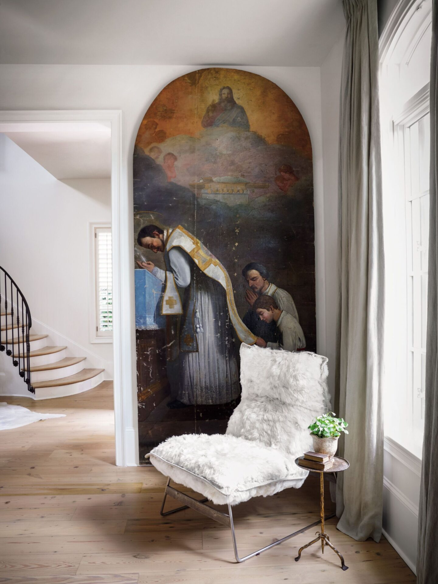 Two massive 19th century ecclesiastical paintings by Victor Mazies mix with a modern alpaca-covered chair in a living room designed by Tara Shaw. #oldworldstyle #tarashaw #religiousart #europeanantiques #interiordesign #rusticelegance