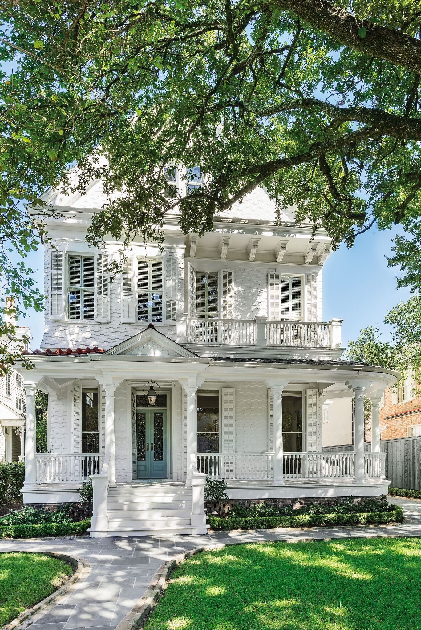 Stately white painted Victorian home has breathtaking architecture and curb appeal in the lower Garden District of New Orleans. #houseexterior #victorianhouses #beautifulwhitehouse #historichome #curbappeal #frontporch