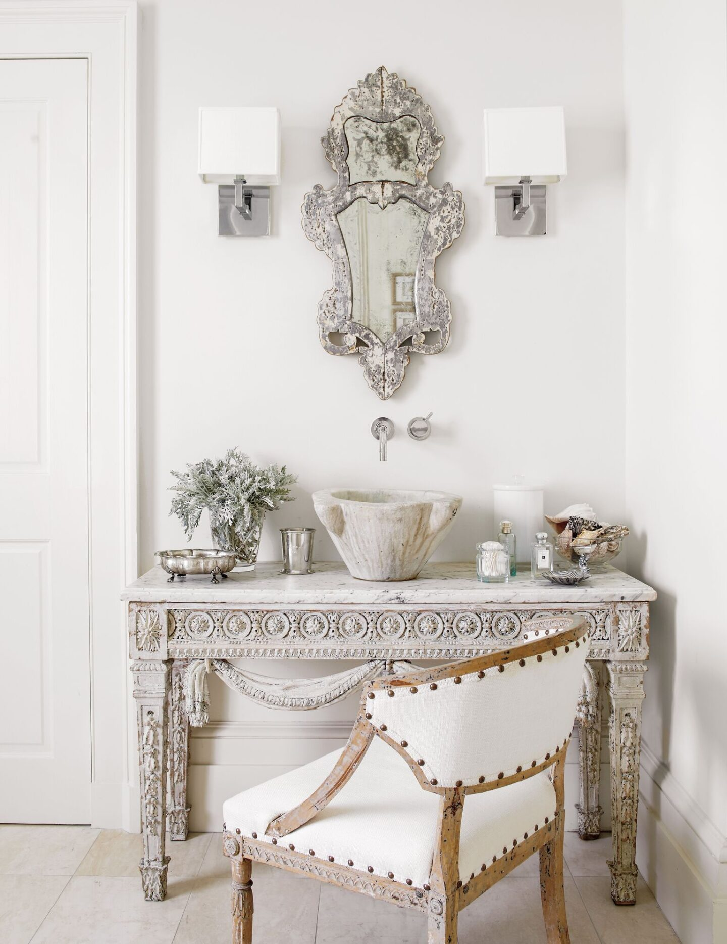 Elegant and luxe, this master bathroom vanity was created from an 18th century French painted console. An 18th century mortar became a sink which Shaw paired with an 18th century Swedish barrel-back chair. #tarashaw #oldworldstyle #interiordesign #antiques #swedishantiques #frenchantiques #stonesink