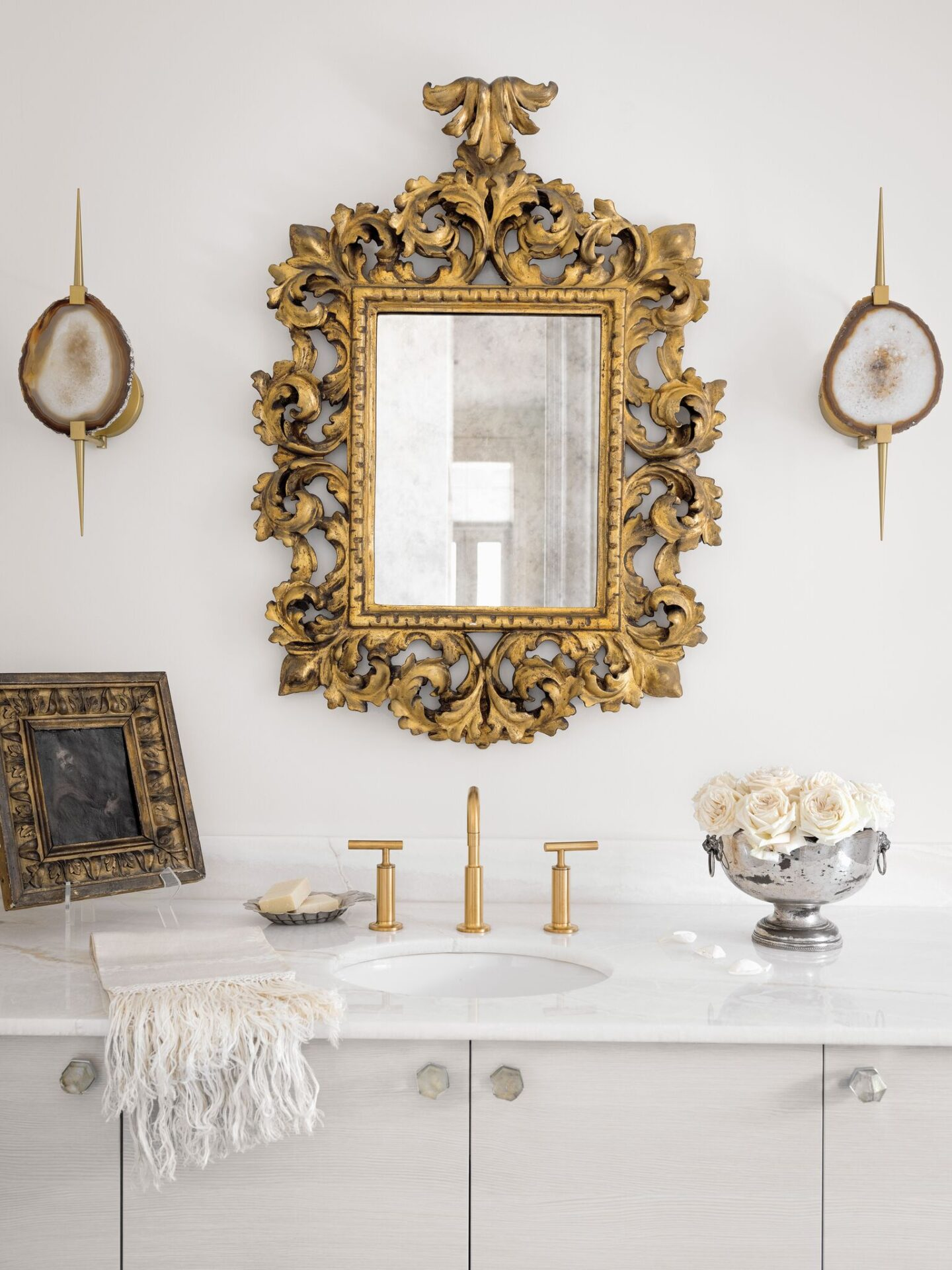 An eighteenth-century rococo Venetian mirror, contemporary onyx sconces, and gold toned fixtures harmonize in a stunningly elegant and luxurious bathroom design. #tarashaw #bathroom #interiordesign #antiques #oldworldstyle #whitebathroom #luxuriousbathroom