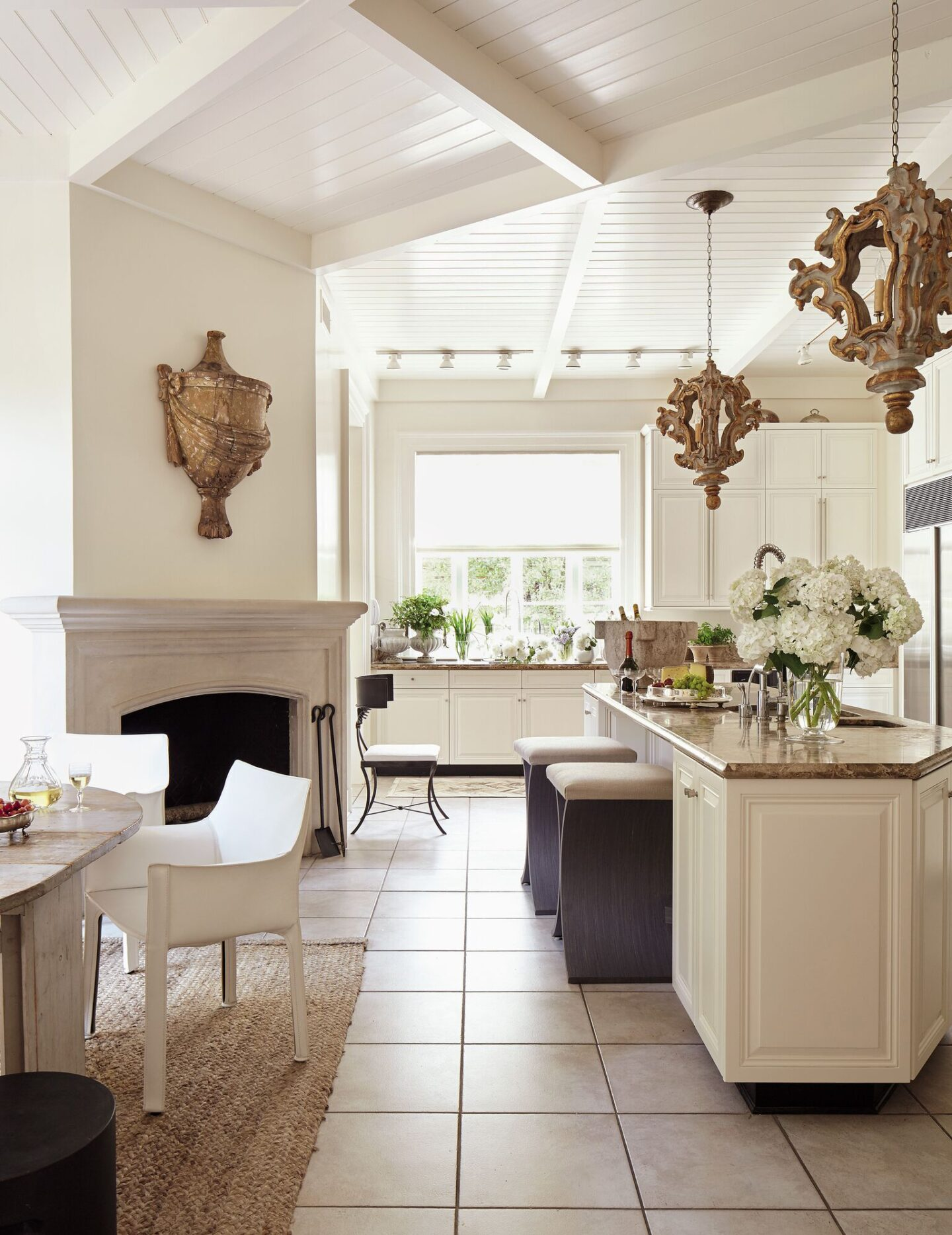 Designer Tara Shaw upgraded a builder's grade kitchen with antiques such as a 19th century urn, 18th century Italian rococo lanterns, and grand stone mortar. #tarashaw #interiordesign #kitchendesign #oldworldstyle #antiques #europeanantiques #whitekitchen #traditionalkitchen #rusticelegance