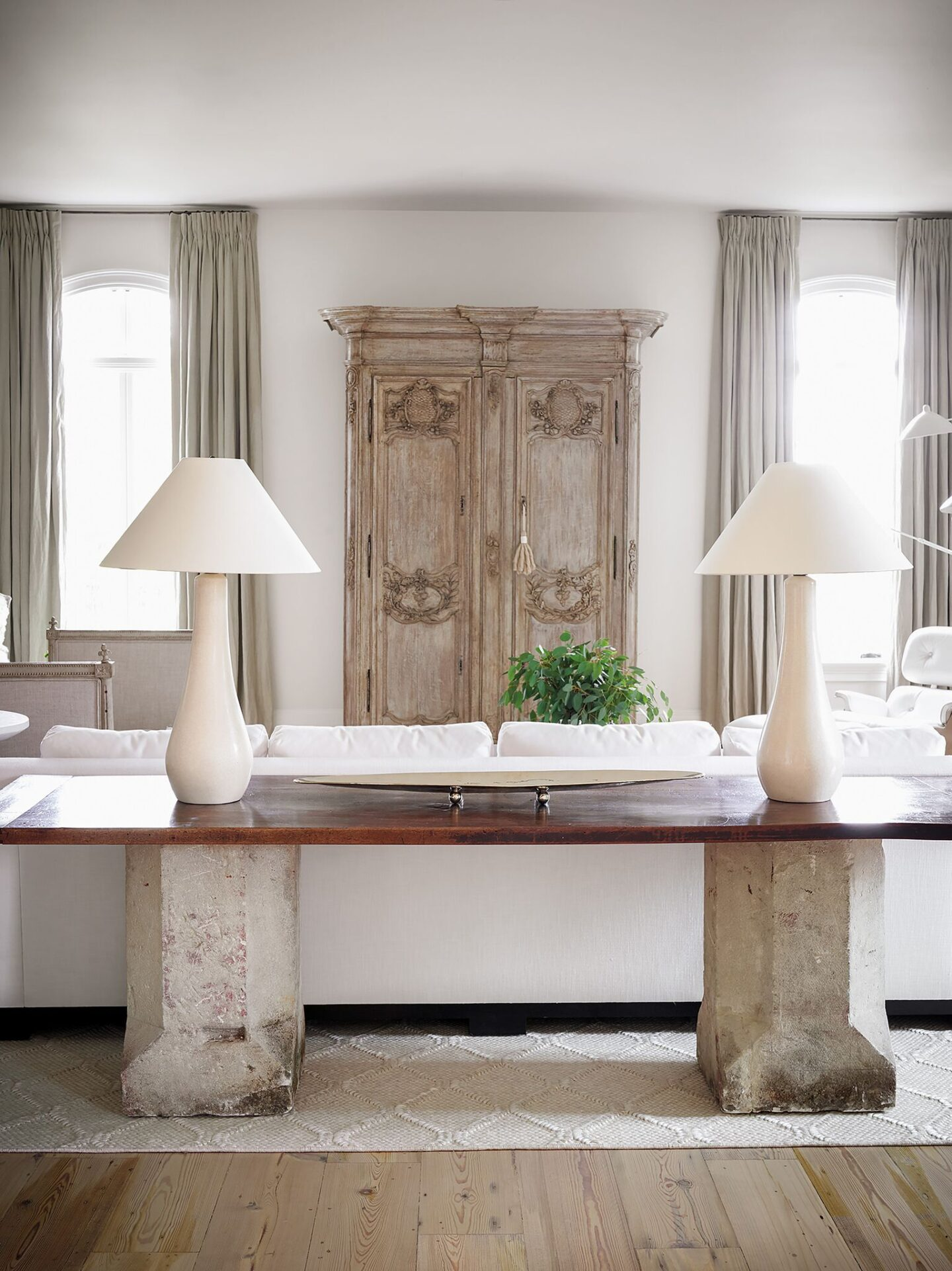 Antique 18th century sandstone garden plinths combine with a 19th century walnut plateau to form a custom console behind the sofa in a living area designed by Tara Shaw. #europeanantiques #oldworldstyle #modernfrench #tarashaw #livingroom #interiordesign
