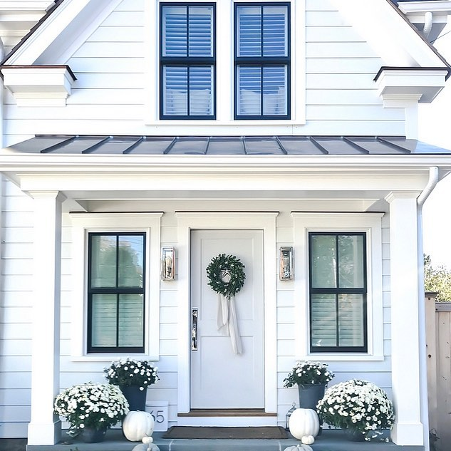 This lovely country farmhouse design features black trim - Design Sixty Five. Charming inspiration if you love white painted house exteriors! #whitehouses #housedesign #exteriors #designinspiration