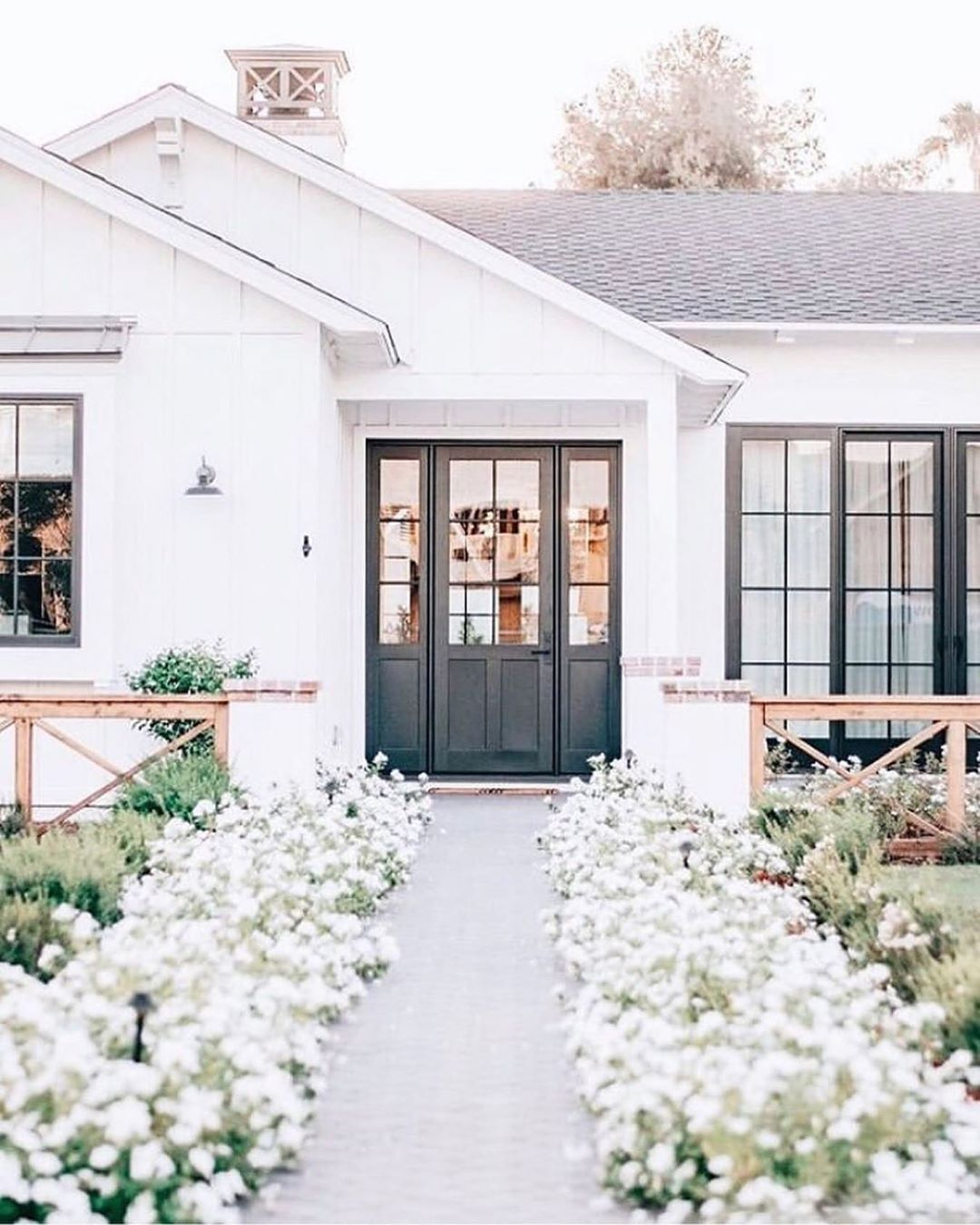 Beautiful white home with black windows and a gorgeous floral flanked path to the front door. Charming inspiration if you love white painted house exteriors! #whitehouses #housedesign #exteriors #curbappeal